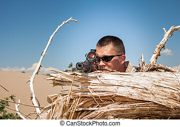 Tactical special ops sniper behind cover of a tree stump in...