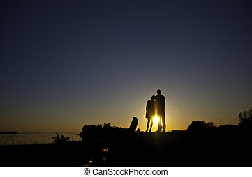 Silouette of two people standing on a bank - Couple standing...