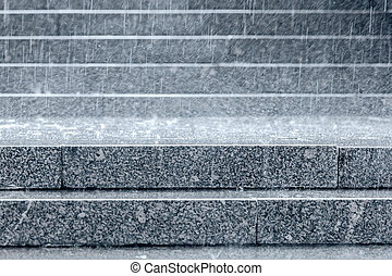 granite steps of staircase with raindrops falling on them...