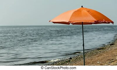 beach umbrella on an empty beach - Orange beach umbrella on...