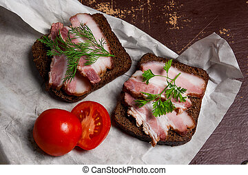 Smoked bacon with rye black bread and cuted tomatoes on the...