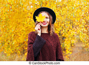 Autumn portrait pretty smiling woman wearing a black hat and...