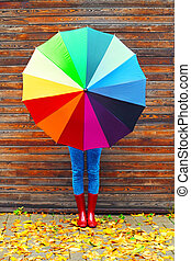 Autumn photo woman holding colorful umbrella wearing a red...