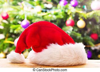 Santa hat against christmas tree background - Santa hat on...