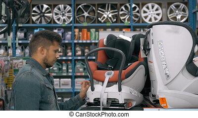 Customer choose child seat in supermarket. Man in car shop...