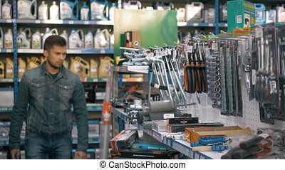 smiling young man purchasing a hand tool in hardware shop...