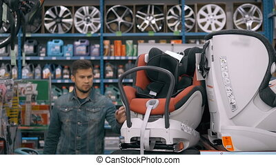 Customer choose child seat in supermarket. Man in car shop...