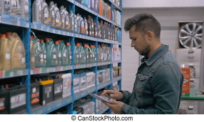 Manager With Tablet PC Checking Goods At Car Supermarket...