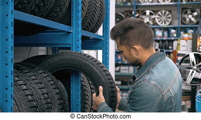 Smiling man auto mechanic carrying new tire in tire store choosing for his car