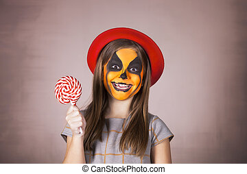 Pretty girl with face painting of a pumpkin