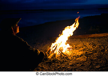 Silhouette of tourist girl around campfire at night on the...