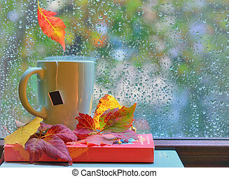 Tea cup at the window with leaves and drops after rain in...