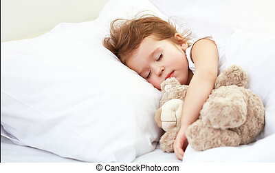child little girl sleeps in the bed with teddy bear - child...