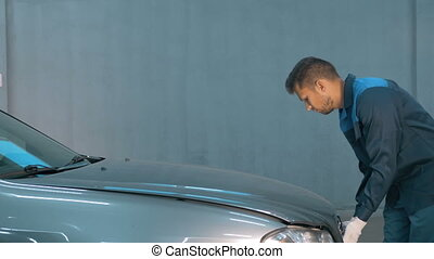 Mechanic checking oil level in a car workshop. Man in truck...