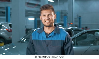 Portrait of Professional smiling car mechanic working in...