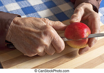 Old woman hands - Old woman slicing an apple
