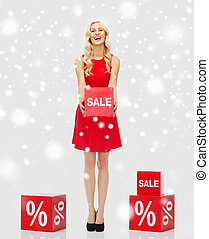 smiling woman with red sale sign over snow - people,...