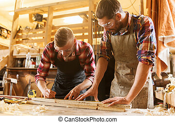 carpenters with ruler and wood plank at workshop -...