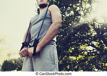 young man exercising with expander in summer park - fitness,...