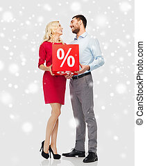 happy couple with red sale sign over snow - people, sale,...