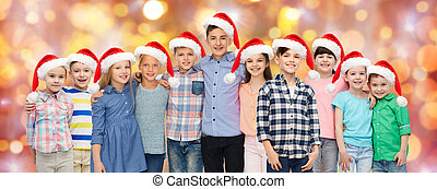 happy smiling children in santa hats hugging - childhood,...