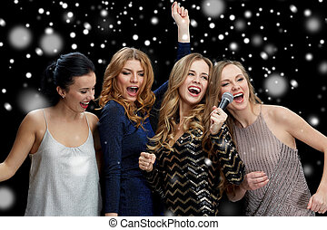 happy young women with microphone singing karaoke - new year...