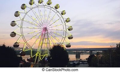 Ferris wheel at sunset on promenade in slowmotion....