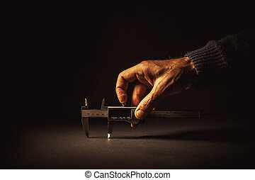 Male Hand Holding a Vernier Caliper - Measuring something...