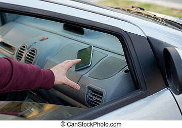 Hand of a thief stealing a mobile phone from a parked