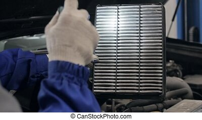 Young Hispanic mechanic changing the oil filter of a car at...