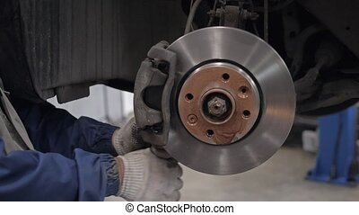 Car mechanic Repairing brakes on car in modern service...