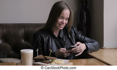 Candid image of young couple smiling in a coffee shop,...