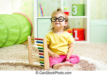 child girl weared glasses playing with abacus toy indoor -...