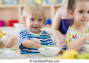 children eating from plates in day care centre - Funny...