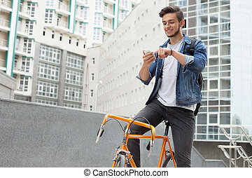 The guy in the blue jeans jacket carries on his shoulder orange bike