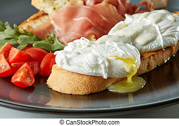 Poached egg on piece of wholegrain bread with vegetables and...