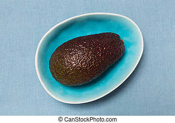 Avocado in a turquoise bowl.