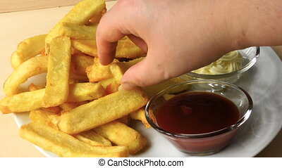 French fries with ketchup and mayonnaise. a potato chip is...
