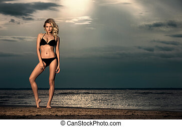 Young woman on beach in bikini. - Young woman posing on...