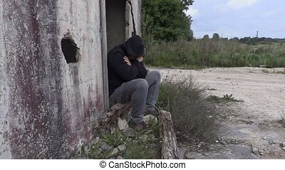 Depressed drug addict with syringe near abandoned building