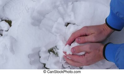 child sculpts a snowball bare hands - child sculpts a...