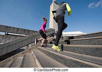 young couple jogging on steps - healthy young couple jogging...