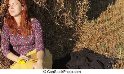 woman resting in the hay on a hot day - young woman resting...
