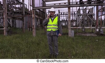 Electrician with folder using smartphone in electrical...