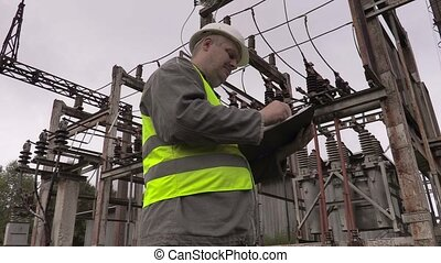 Electrician writing in electrical substation