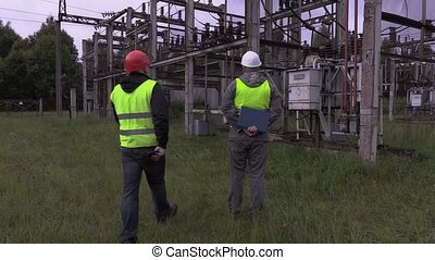 Electricians talking in electrical substation