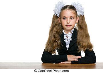 Schoolgirl sits at the school desk