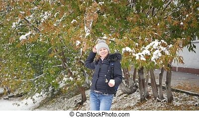 girl throws a snowball in the autumn park