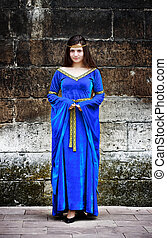medieval woman stand against the stone wall