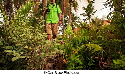 Tourist Old Man Works Way through Thick Bushes in Park -...